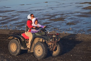 Eskimo woman and child on ATV
