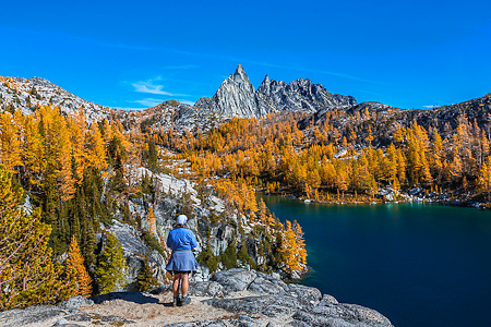Hiker with Prusik Peak and Perfection Lake in Autumn in The Ench