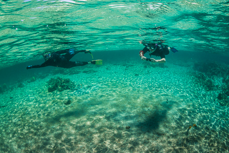 Snorkelers Reflections at Kapoho off Big Island of Hawaii