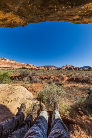 Backpackers resting under a rock overhang within Salt Creek Canyon in The Needles District of Canyonlands National Park, Utah, USA