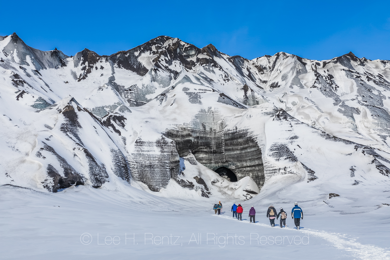 Adventurers walking toward an ice cave entrance in a lobe of Mýrdalsjökull Glacier, which sits atop Katla Volcano, in winter in Iceland
