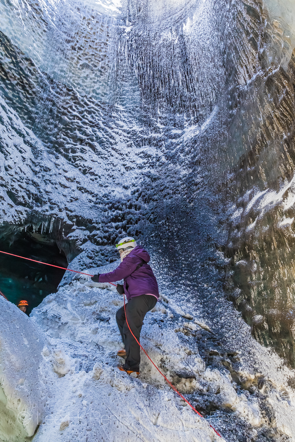 Karen Rentz using rope and crampons to ascend to cave entrance during ice cave tour to a lobe of Mýrdalsjökull Glacier, which sits atop Katla Volcano, in winter in Iceland